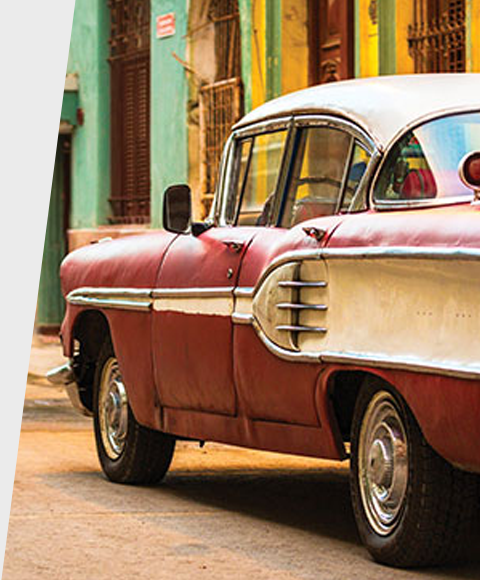 Classic car parked on a colorful Cuban calle