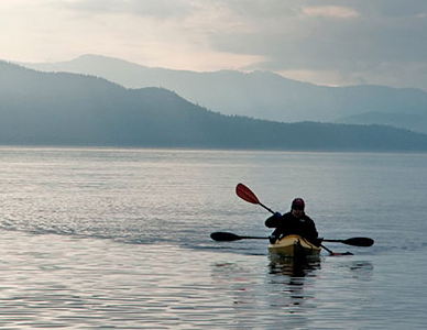 A kayaker on a lake in Alaska, mountains in the distance