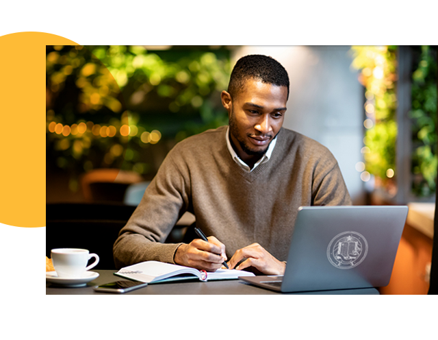 Man Taking Notes Watching Laptop